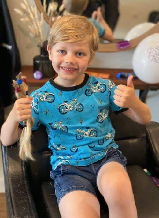 Harry Grantham holding his hair donation